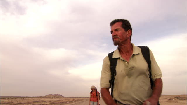 a stranded traveler helps his companion walk down a desert road. - survival stock videos & royalty-free footage