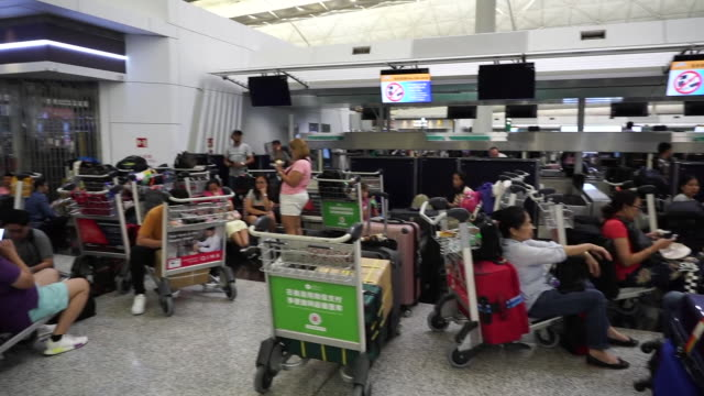 stranded travellers resting in the check-in area of hong kong airport after it was occupied by protesters - 香港国際空港点の映像素材/bロール