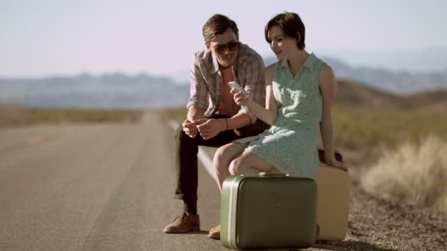 Stranded young couple on a lonely desert road type on smartphone