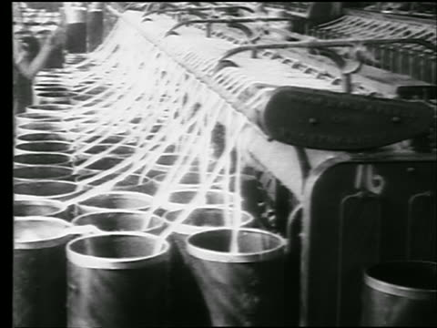 b/w 1922 strands of cotton being pulled from containers into machine / female worker walks by / news - textile mill stock videos & royalty-free footage