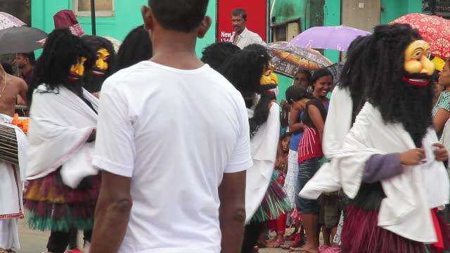 stockvideo's en b-roll-footage met ms pan strange masks and costumes adorn dancers in seenigama annual perahera parade audio / sinigama, southern province, sri lanka - sri lankaanse cultuur