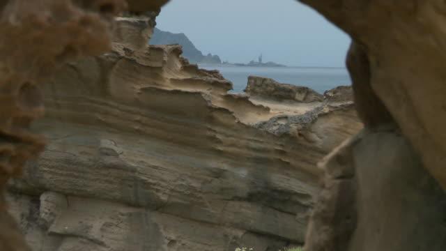 strange shaped rock at beach in yeliu, taiwan - ロックストラータ点の映像素材/bロール