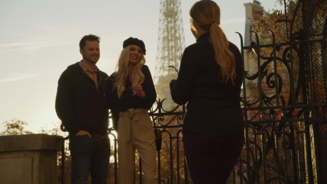 vidéos et rushes de stranger using cell phone to photograph couple near eiffel tower / paris, ile de france, france - prendre une photo