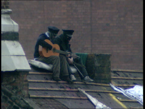strangeways prison riot: day 2; banner hanging from window `no dead' on it: prisoners on roof one playing guitar as others dancing about: group on... - hm prison manchester stock videos & royalty-free footage
