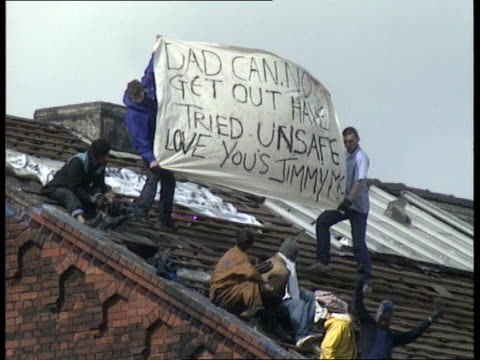 prisoners continue siege mr mrs mcdermott standing at railing jimmy shouting from roof intvw lilly mcdermott jimmy with others on roof with banner... - hm prison manchester stock videos & royalty-free footage