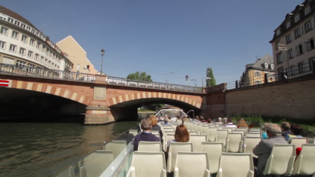 vídeos de stock e filmes b-roll de hd strasbourg. colorful medieval buildings seen from a boat tour across ill river. we can see the ship and the tourist in foreground and the river and bridges in the background. - estrasburgo