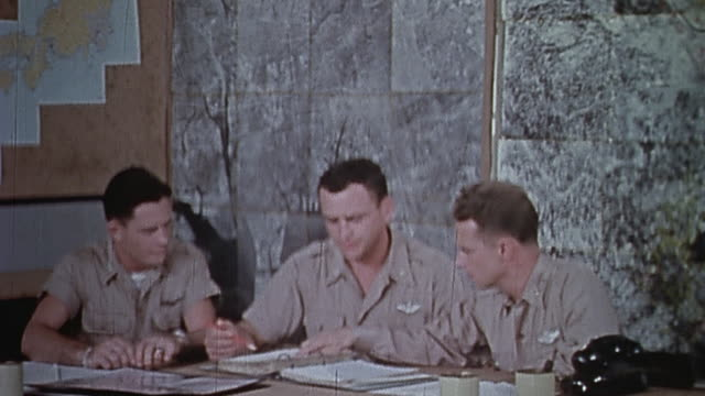 vídeos de stock, filmes e b-roll de usaaf strategists planning air raid on tokyo / mariana islands - enfoque de objeto sobre a mesa