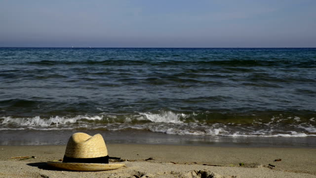 straw hat on the sand in front of the sea. - straw hat stock videos & royalty-free footage