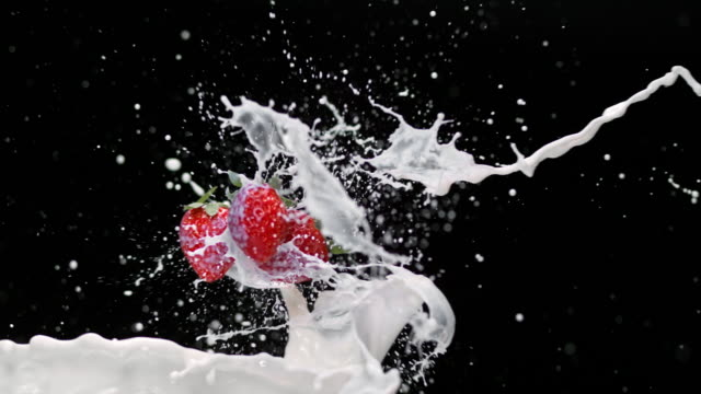 SLO MO Strawberries being splashed by milk in the air