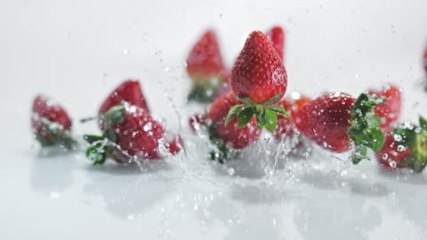 vidéos et rushes de slo missouri ld fraises couvertes de rebondir sur une surface de l'eau - freshness