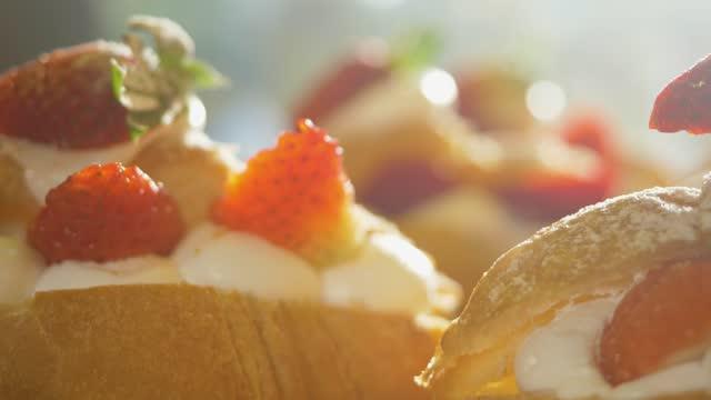 stockvideo's en b-roll-footage met strawberries cream cheese on toast in window display with sunlights, slow motion. - langzaam