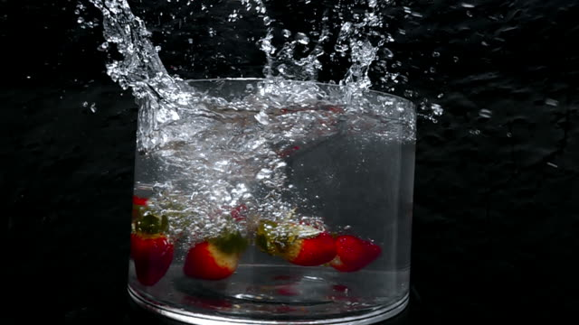 strawberries fall into a large bowl of fresh water creating a splash as the camera revolves around it in slow motion. - david ewing stock videos & royalty-free footage