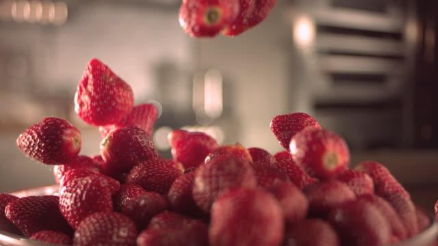 vídeos y material grabado en eventos de stock de strawberries falling into a glass bowl. - fresa
