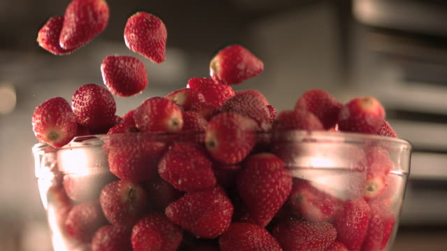 vidéos et rushes de strawberries falling into a glass bowl. - antioxydant