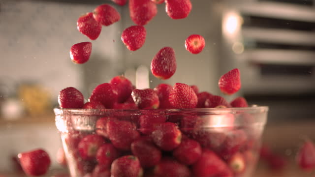 vidéos et rushes de strawberries falling into a glass bowl. - coupe à fruits