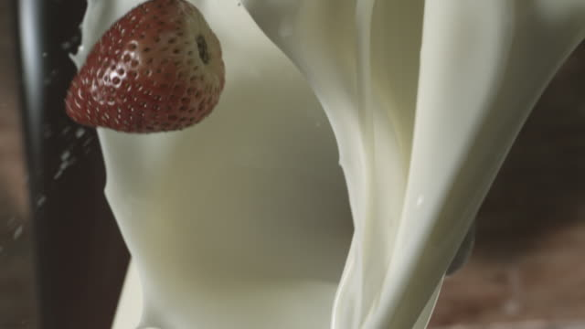 Strawberries falling into pouring creme.