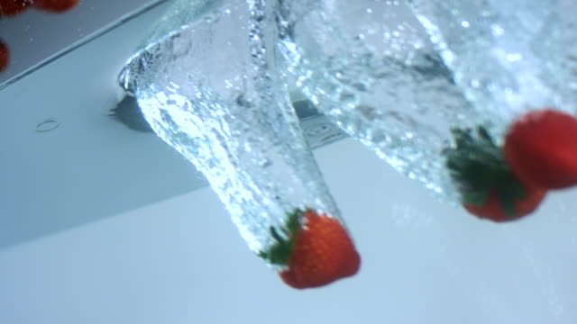 slo mo cu strawberries falling into water - medium group of objects stock videos & royalty-free footage