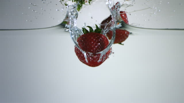 slo mo cu strawberries falling into water - strawberry stock videos & royalty-free footage