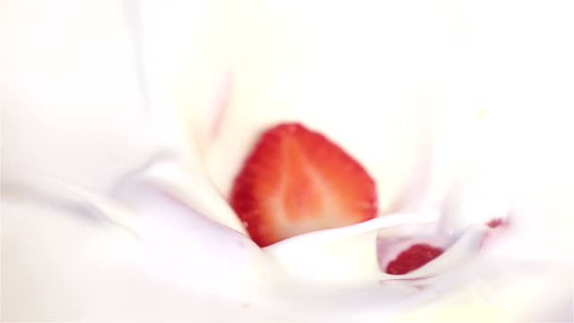 strawberries falling into yogurt in real slow motion - whipped food stock videos and b-roll footage
