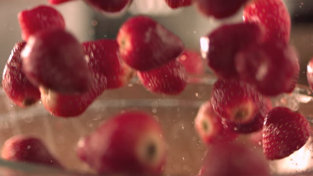 vidéos et rushes de strawberries falling onto strawberries in a glass bowl. - coupe à fruits