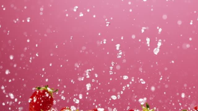 vídeos y material grabado en eventos de stock de strawberries falling - pink color