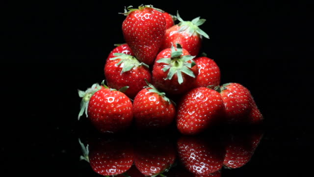 Strawberries gradually illuminated from darkness.
