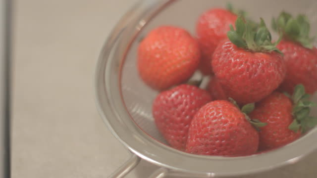 strawberries in a strainer - static shot - medium group of objects stock videos & royalty-free footage