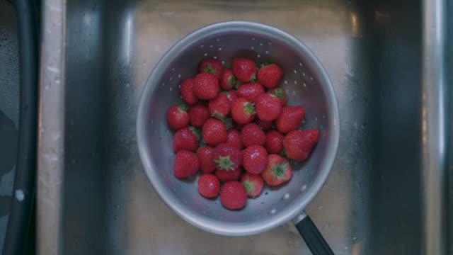 vídeos y material grabado en eventos de stock de strawberries in colander in sink - fresa