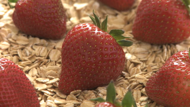 strawberries on a bed of oats - medium group of objects stock videos & royalty-free footage