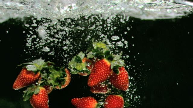 vídeos de stock, filmes e b-roll de strawberries underwater in super slow motion - grupo médio de objetos