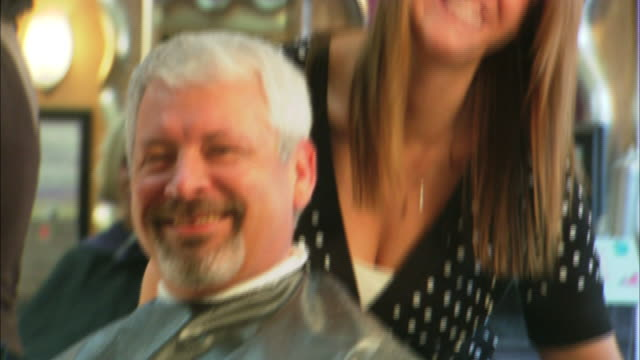 strawberry blond hairdresser standing behind a graying, mature adult man who is sitting in a salon chair