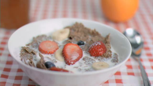 stockvideo's en b-roll-footage met strawberry falling in super slow motion in cereal bowl - tafelkleed