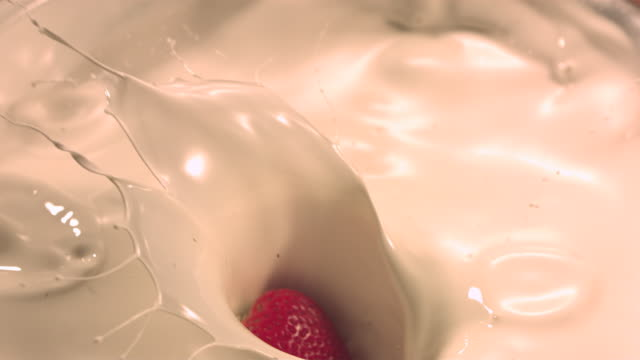 Strawberry falling into cream milk