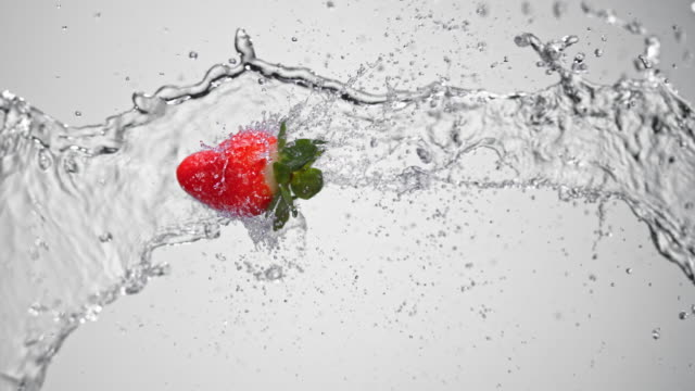 SLO MO Strawberry flying through a water splash in the air