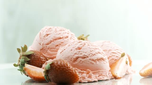 Strawberry ice cream garnished with fresh strawberries beside