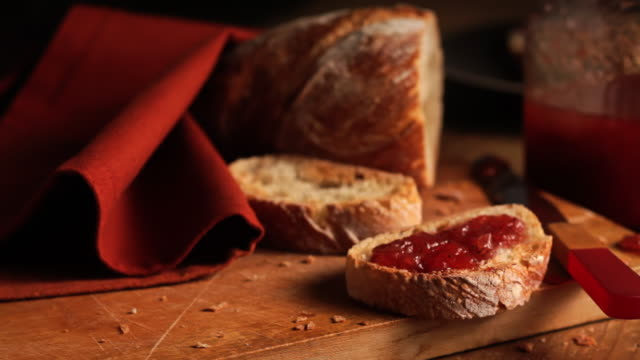 strawberry jam coats a slice of rustic bread. - bread stock videos & royalty-free footage