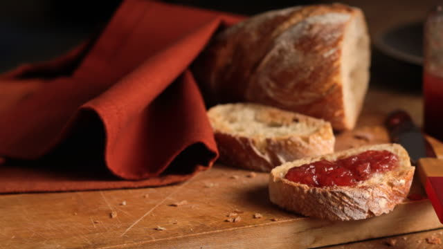 Strawberry jam covers a slice of rustic bread.