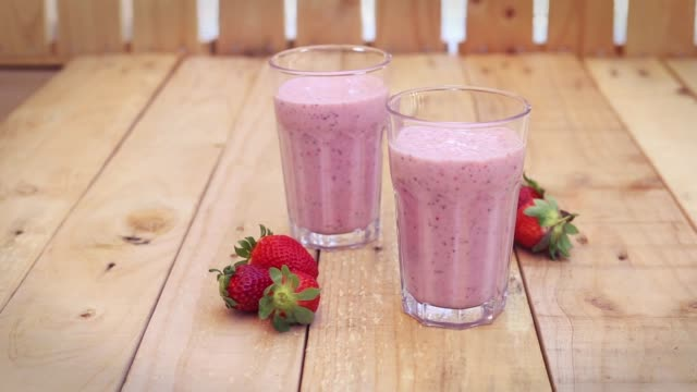 strawberry milkshakes on a wood table outdoors - strawberry milkshake stock videos & royalty-free footage