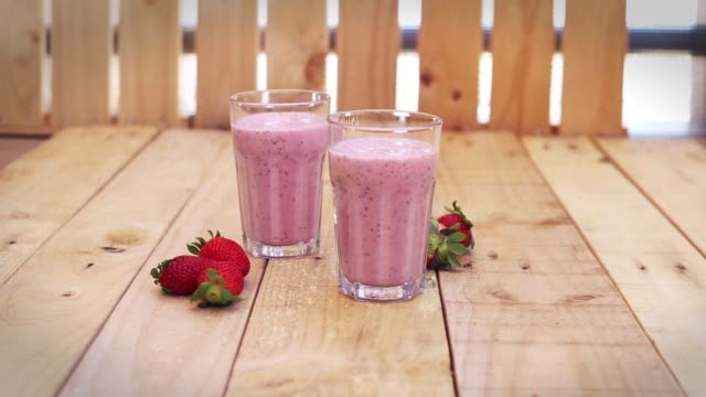 strawberry milkshakes with chia seeds in glasses on a wood table - strawberry milkshake stock videos & royalty-free footage