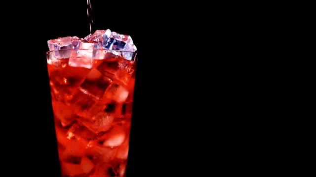 vidéos et rushes de versant rouge de soude dans un verre de glace au ralenti sur fond noir - verre d'eau