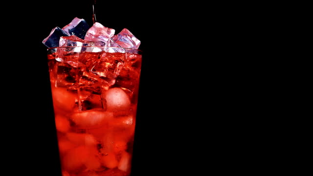 Pouring red soda into  a glass of ice at slow motion on a black background