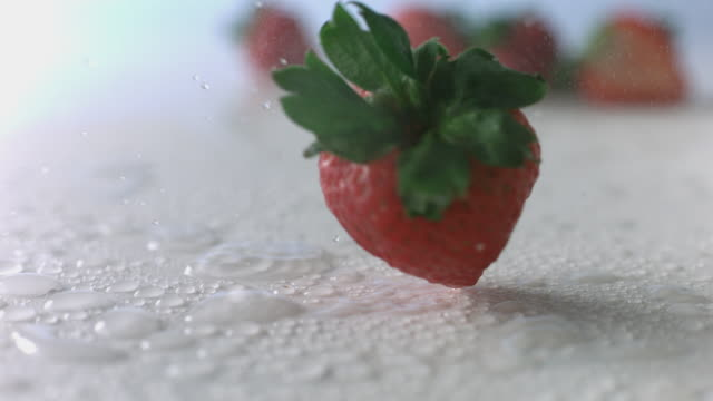 strawberry spins like a top through mist on wet, white surface - small group of objects stock videos & royalty-free footage