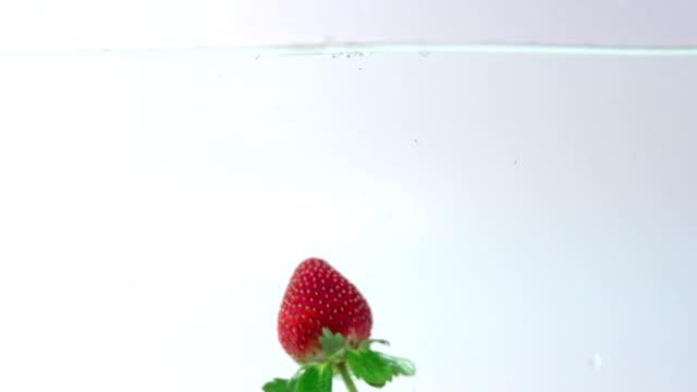vídeos y material grabado en eventos de stock de strawberry zambulléndose en el agua en cámara lenta - fresa