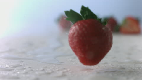 strawberry tumbles and spins like a top through mist on wet, white surface - small group of objects stock videos & royalty-free footage