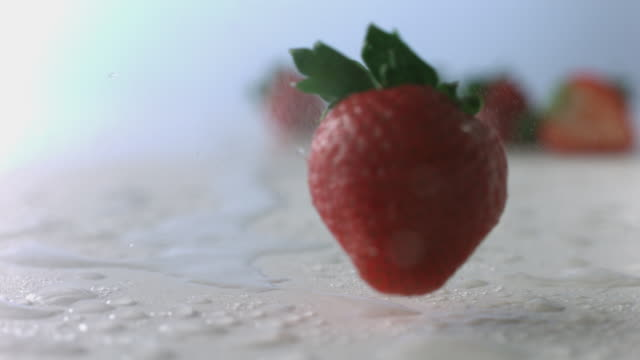 stockvideo's en b-roll-footage met strawberry tumbles and spins like a top through mist on wet, white surface - vijf dingen