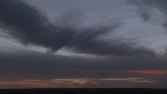 vídeos y material grabado en eventos de stock de streaky gray cirrus clouds hover above a flat landscape. - cirro