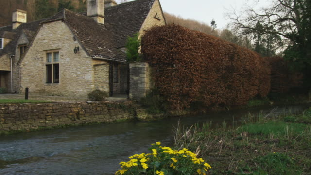 vídeos de stock, filmes e b-roll de ms pan stream and stone houses, castle combe, united kingdom - cultura inglesa