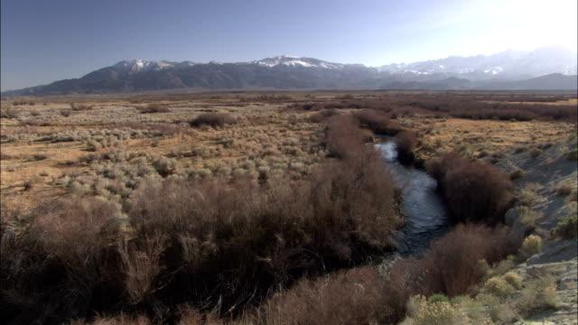 a stream flows through a valley near the sierra nevada mountain range. - amerikanische sierra nevada stock-videos und b-roll-filmmaterial