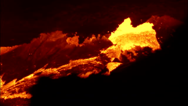 A stream of molten lava bubbles and roils across volcanic rock. Available in HD.