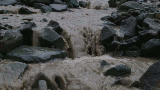 vídeos de stock e filmes b-roll de stream of mud flows, slow motion - fundição